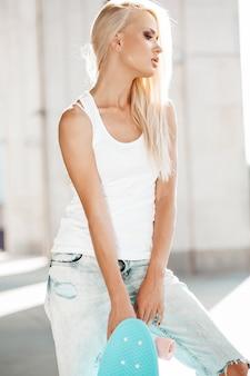 Portret van mooi schattig blond meisje in witte t-shirt en jeans die in openlucht stellen