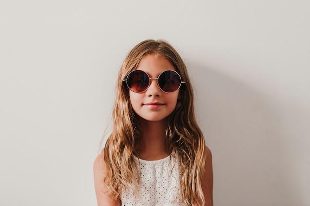 Portret van mooi tienermeisje thuis. zitten en moderne zonnebril dragen. geluk en levensstijlconcept
