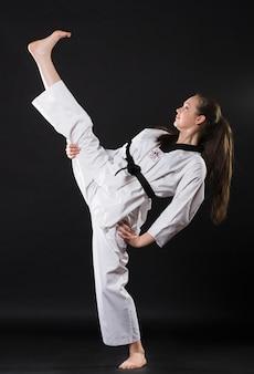 Portret van mooi vechtsportenmeisje dat in kimono karatekata uitoefent tegen donkere achtergrond