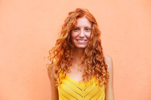 Portret van mooi vrolijk roodharigemeisje met vliegend krullend haar glimlachen