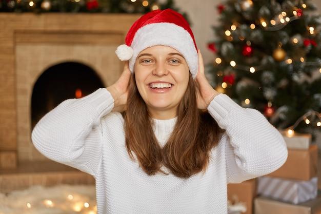 Portret van mooi vrouwelijk model dat kerstmuts en witte trui draagt, handen op haar hoofd houdt, poseren in de woonkamer met open haard en kerstboom, meisje blij om nieuwjaar te vieren.
