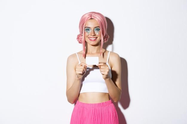 Portret van mooi vrouwelijk model dat roze pruik draagt voor halloween-feest, vakantie viert en creditcard toont, permanent.
