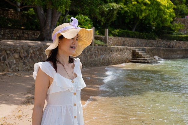 Portret van mooie 40-jarige aziatische vrouw op het strand.