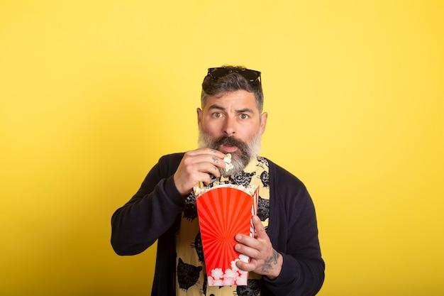 Portret van mooie aantrekkelijke bezorgd bang verslaafde bebaarde man met geel shirt en blauwe jas eten popcorn snack kijken naar enge video geïsoleerd op gele achtergrond.