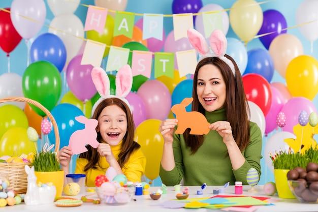 Portret van mooie aantrekkelijke blije creatieve vrolijke vrolijke meisjes die plezier hebben in handen papier konijnen handwerk illustraties genieten van vrije tijd kleine zusje