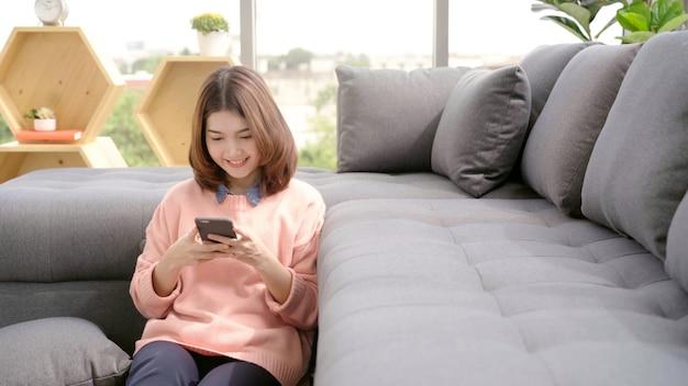 Portret van mooie aantrekkelijke jonge glimlachende aziatische vrouw die smartphone gebruiken terwijl het liggen op de bank