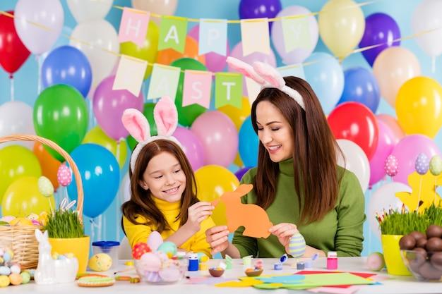 Portret van mooie aantrekkelijke mooie blije vrolijke vrolijke meisjes vrienden vriendschap met plezier voeden papier konijn decor kunstwerk genieten van vrije tijd