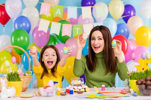 Portret van mooie aantrekkelijke mooie creatieve blije vrolijke vrolijke meisjes die gekleurde eieren in de hand houden handwerk kunstwerk aanwezig cadeau april masterclass klein zusje