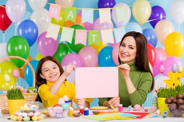 Portret van mooie aantrekkelijke mooie creatieve vrolijke vrolijke meisjes in handen houden blanco papier handwerk creëren april dag heldere levendige glans levendige blauwe kleur