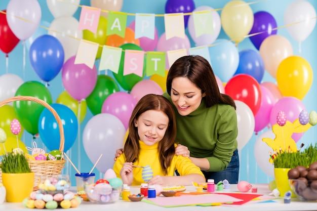 Portret van mooie aantrekkelijke mooie schattige voorzichtige creatieve vrolijke vrolijke meisjes die het maken van feestelijke handgemaakte decor april dag heldere levendige glans levendige blauwe kleur voorbereiden