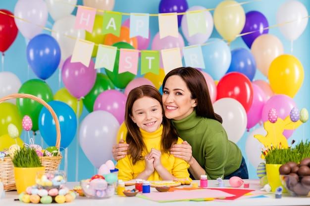 Portret van mooie aantrekkelijke mooie zorgvuldige creatieve vrolijke vrolijke meisjes voorbereiding feestelijke decor april dag knuffelen heldere, levendige glans levendige blauwe kleur