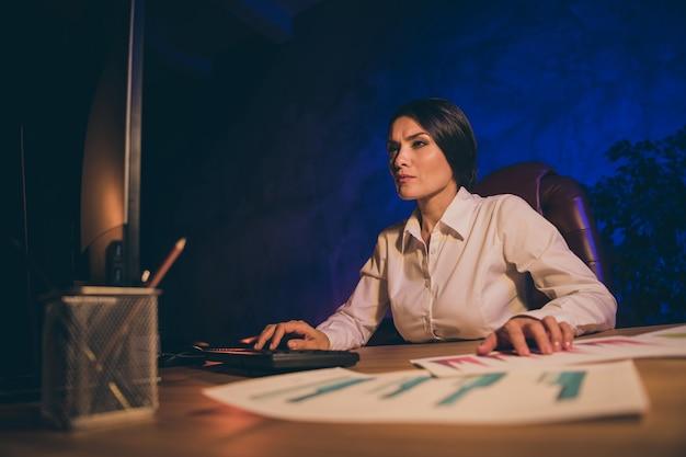 Portret van mooie aantrekkelijke stijlvolle bekwame dame topmanager verslag voorbereiden geld salaris valuta verhouding resultaat rente investeren analyseren economie accountantscontrole 's nachts donkere werkplek station