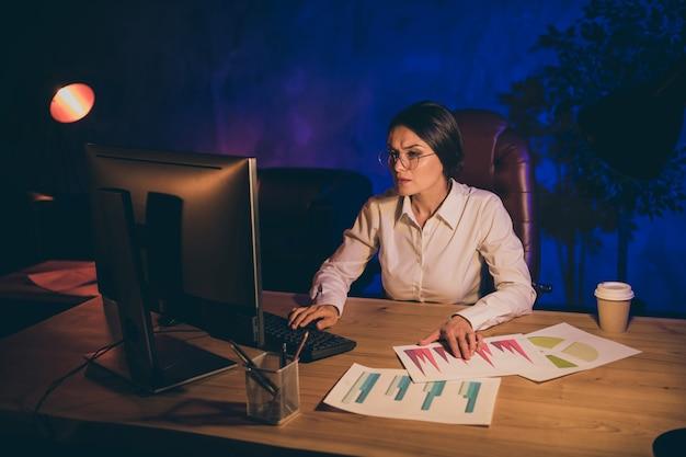 Portret van mooie aantrekkelijke stijlvolle dame top uitvoerend manager bedrijf agentschap eigenaar verslag voorbereiden strategie investeringsverhouding resultaat analyseren economie audit 's nachts donkere werkplek station
