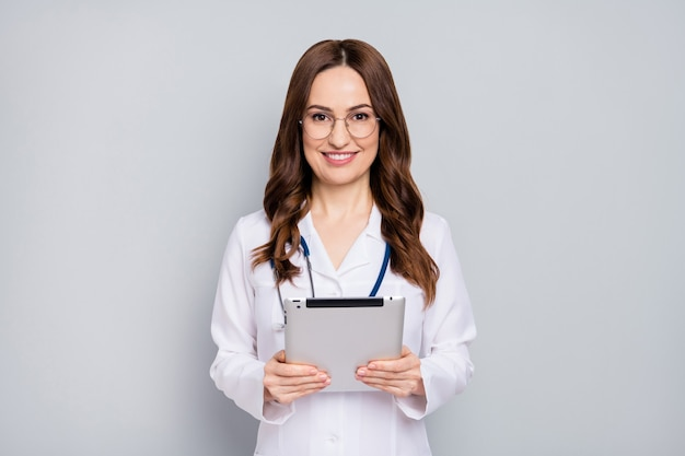 Portret van mooie aantrekkelijke vrij vrolijke golvendharige doc met phonendoscope stethoscoop in handen houden ebook diagnostisch centrum kliniek geïsoleerd over grijze pastel kleur achtergrond