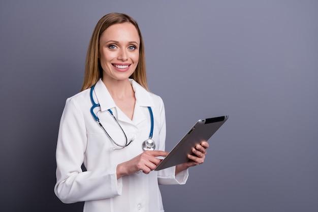 Portret van mooie aantrekkelijke vrolijke blonde meisje doc met behulp van de gadget