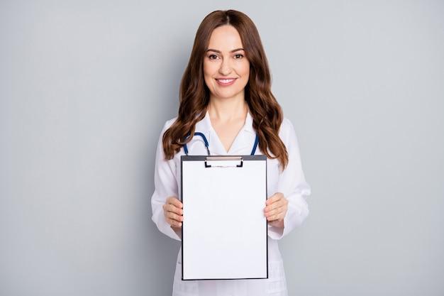 Portret van mooie aantrekkelijke vrolijke golvendharige doc phonendoscope stethoscoop demonstreren lege copyspace document teken kliniek assistentie geïsoleerd over grijze pastelkleur achtergrond