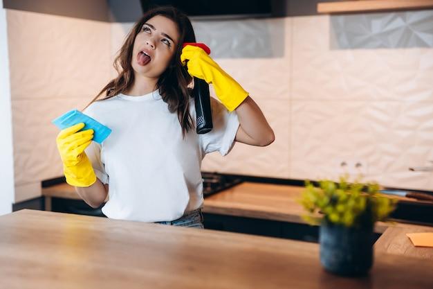 Portret van mooie aantrekkelijke vrouw huisvrouw met behulp van spray met plezier in modern licht wit interieur keuken huis lijkt het haar saai