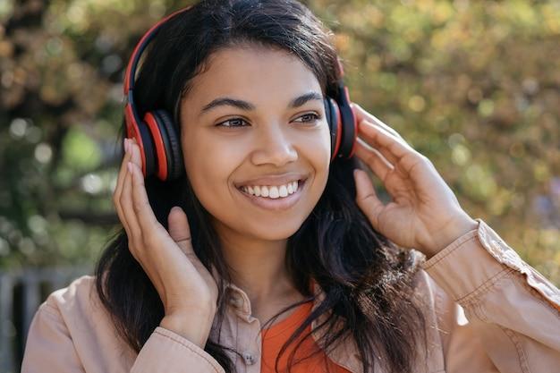 Portret van mooie african american vrouw, luisteren naar muziek op de koptelefoon, glimlachend