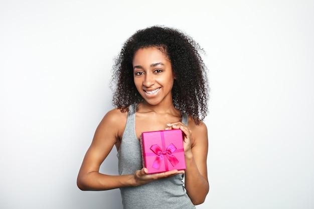 Portret van mooie afrikaans-amerikaanse vrouw met giftdoos op witte achtergrond