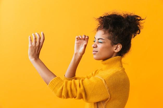 Portret van mooie afrikaanse amerikaanse vrouw die met afrokapsel door onzichtbare geïsoleerde kijker kijkt
