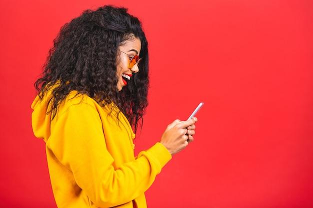 Portret van mooie afrikaanse amerikaanse vrouw met zonnebril die telefoon met behulp van