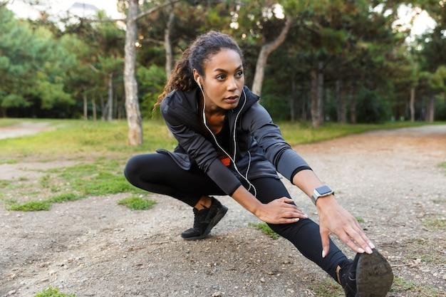 Portret van mooie afrikaanse amerikaanse vrouwen20s die zwarte trainingspak dragen die oefeningen doen, en haar benen in groen park strekken