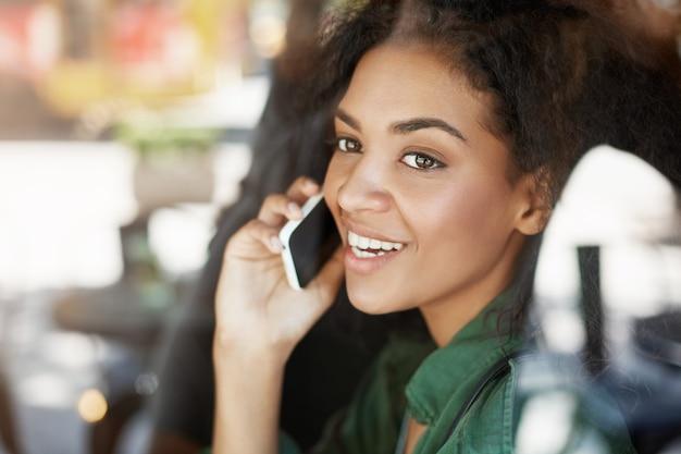 Portret van mooie afrikaanse vrouw achter glas glimlachen praten over de telefoon