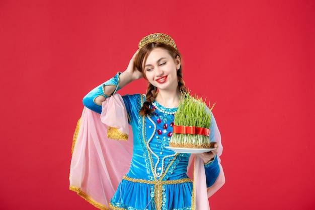 Portret van mooie azeri vrouw in traditionele kleding met semeni op rood