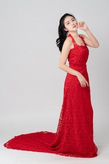 Portret van mooie aziatische bruid die rood op wit draagt