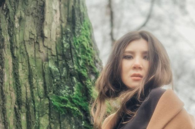 Portret van mooie aziatische dame die zich door de boom met mos in de late herfst bevindt.