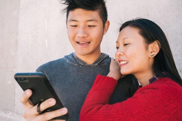 Portret van mooie aziatische paar kijken naar de mobiele telefoon terwijl goede tijd samen doorbrengen