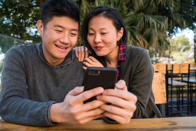 Portret van mooie aziatische paar kijken naar de mobiele telefoon zittend en tijd doorbrengen in de coffeeshop.