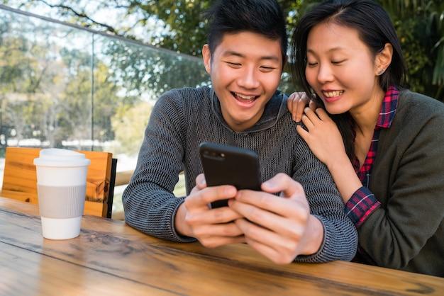Portret van mooie aziatische paar kijken naar de mobiele telefoon zittend en tijd doorbrengen in de coffeeshop