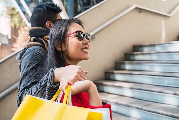 Portret van mooie aziatische paar kleurrijke boodschappentassen houden en genieten van winkelen