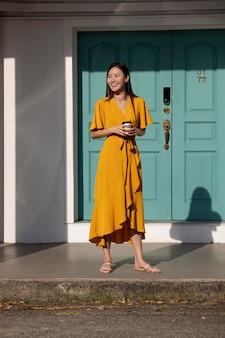 Portret van mooie aziatische vrouw die buiten in de stad poseert terwijl ze koffie drinkt
