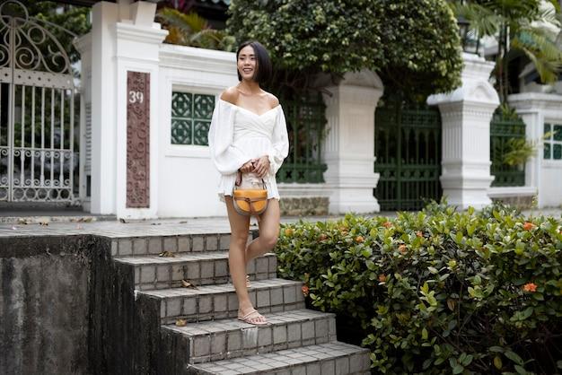 Portret van mooie aziatische vrouw die buiten in een witte jurk poseert