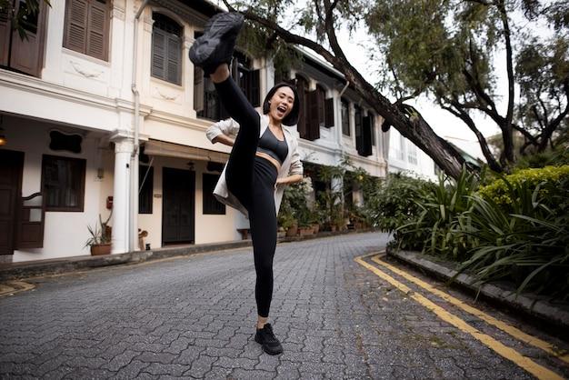 Portret van mooie aziatische vrouw die buiten in sportieve outfit poseert
