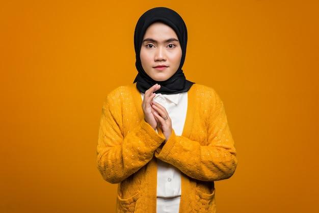 Portret van mooie aziatische vrouw die een gele cardigan draagt
