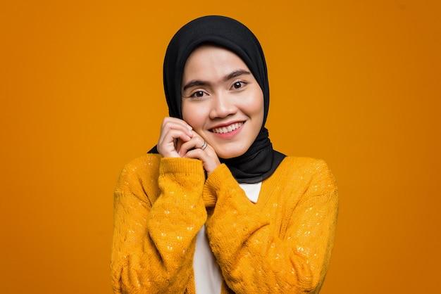 Portret van mooie aziatische vrouw die en een geel vest glimlacht draagt