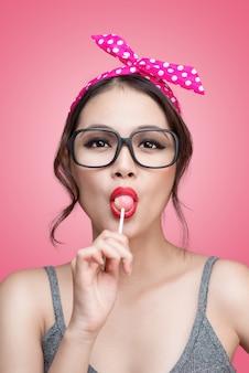 Portret van mooie aziatische vrouw die hartvorm lolly eet, gekleed en make-up in pin-up stijl op roze achtergrond.
