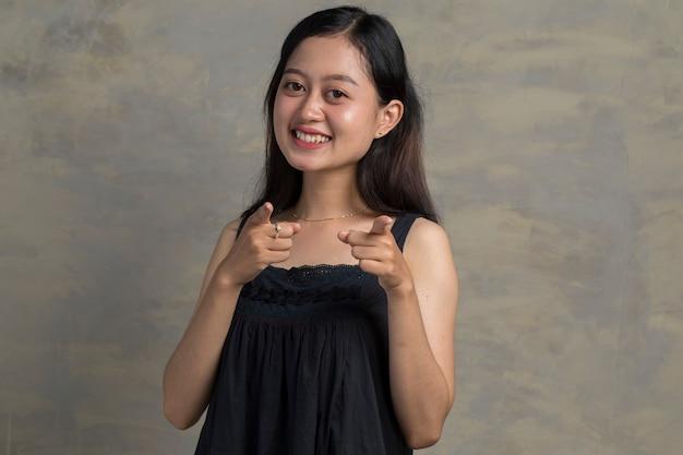Portret van mooie aziatische vrouw die lacht terwijl vooruit wijst