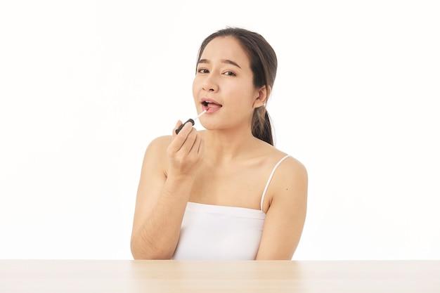 Portret van mooie aziatische vrouw die lippenstift toepast