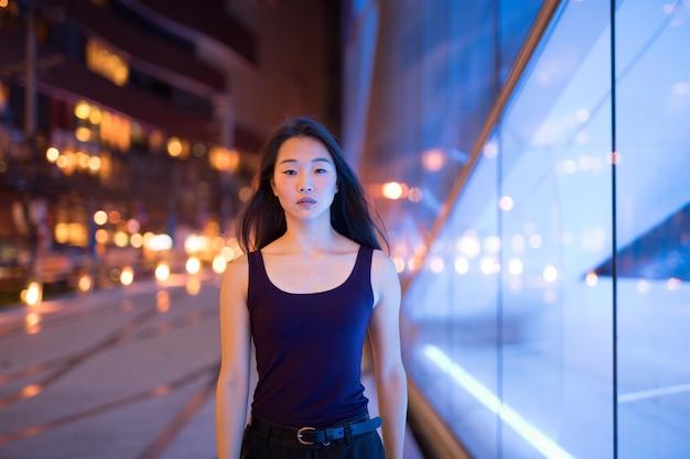 Portret van mooie aziatische vrouw die 's nachts buiten loopt