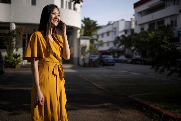 Portret van mooie aziatische vrouw die smartphone buiten in de stad gebruikt