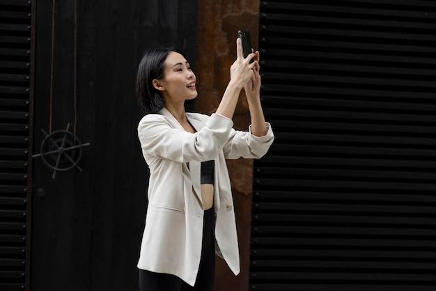 Portret van mooie aziatische vrouw die smartphone buitenshuis gebruikt