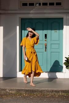 Portret van mooie aziatische vrouw in gele jurk poseren buiten in de stad