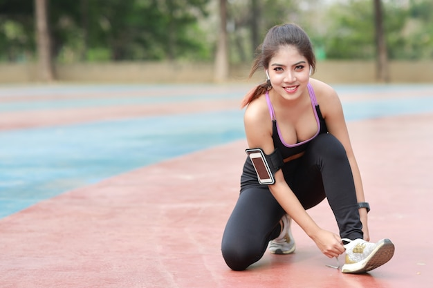 Portret van mooie aziatische vrouw in sportkleding joggen buiten met slanke atletische benen. sportieve meisjeshanden nemen pauze en schoen strikken. na training. gezond en lifestyle outdoor concept