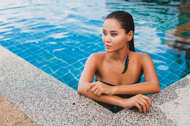 Portret van mooie aziatische vrouw in zwarte zwembroek badend luxe spa zwembad dragen sylish veer oorbel glimlachend, sexy, slank gebruind lichaam en natte huid, zomer stijl accessoires,