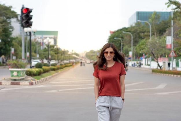 Portret van mooie aziatische vrouw met lang haar die zonnebril dragen die op straat lopen