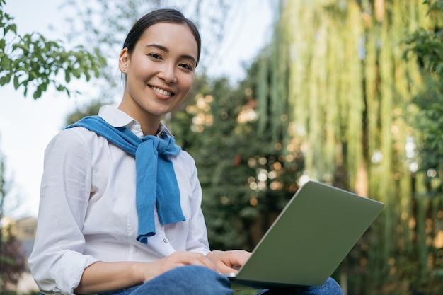 Portret van mooie aziatische vrouw met laptopcomputer, online werken, zittend in het park